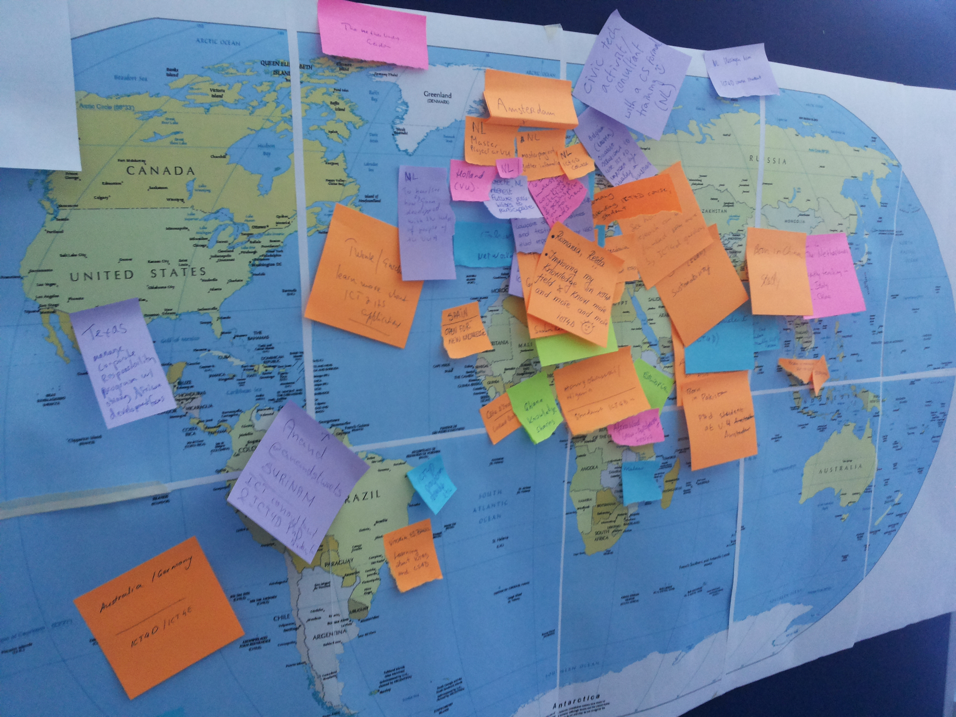 The board shows the location of origin of the participants. There are five color post-its indicating the background (orange = computer scientist, pink = social scientists, blue =ict4d practitioners, green=development practitioners and purple = other). The results show a wide geographical spread of participants.